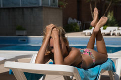 Sexy girl in sun lounger on swimming pool Royalty Free Stock Photo