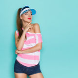 Sexy Girl In Sun Visor Cap. Beautiful young woman in pink striped shirt, jeans shorts and blue sun visor posing with hand on chin and looking away. Three quarter Royalty Free Stock Photography