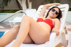Sexy girl sunbathing by the pool. Gorgeous young woman in a bikini relaxing on a poolside bench and getting a tan Stock Photography