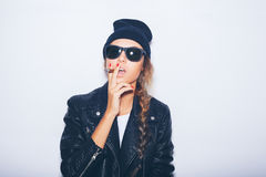 Sexy girl in sunglasses and black leather jacket smoking cigar Stock Image