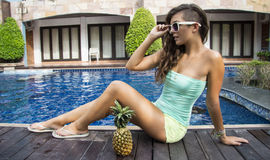 Sexy girl with sunglasses sitting near swimming pool Royalty Free Stock Images