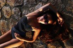 Girl in sunglasses.sunbathing. Girl in sunglasses lying on rocks and sunbathing.beautiful fashion woman in bikini stock photo