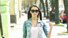 Sexy girl with sunglasses walking on a camera. Slowly stock video