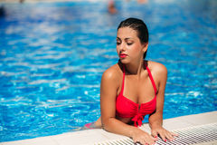 A girl is swimming in the swimming pool near the beach, sunny weather. Summer. Girl in a pink bathing suit on the beach. Summer. Sunny weather. Beautiful stock image