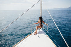 Sexy girl in swimwear on yacht in tropics Stock Images