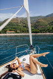 Sexy girl in swimwear on yacht in tropics Stock Photography