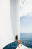 Sexy girl in swimwear on yacht under big white sail Royalty Free Stock Images