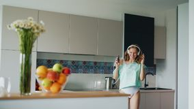 girl in t-shirt singing and dancing in kitchen. Happy woman in underwear stock video footage