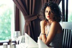 Girl at table. Beautiful girl sitting at restaurant table looking at camera royalty free stock photo