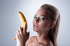 Sexy girl take long banana like gun Royalty Free Stock Image