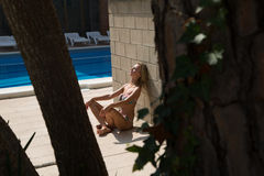 Sexy girl takes a sunbath on swimming pool Stock Images