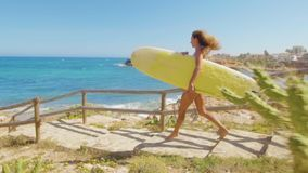 Sexy girl with tanned skin walking along the beach with surfboard. Beautiful young woman in bikini swimsuit. Concept of stock footage