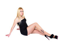 Sexy girl with tattoo. Sexy girl with a tattoo sitting on the floor leaning on hands, isolated on white Stock Photos