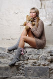 Sexy girl with teddy bear sitting on wall. In short erotic dress and perfect legs Royalty Free Stock Photography