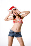 Sexy girl tongue sticking out. Young sexy woman wearing Santa hood bikini top and short jeans tongue sticking out expression Royalty Free Stock Image