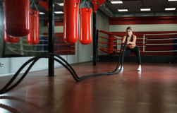 Sexy girl training with a rope shot in a gym Stock Image