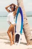 girl on tropical beach with surf board. Stock Photos