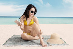 Sexy girl using sunscreen at seashore Royalty Free Stock Images