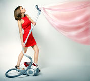 Sexy girl using vacuum cleaner Royalty Free Stock Image