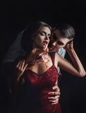 Sexy girl vampire. In passionate embrace man's hands, stained with blood, the girl in a red dress, a fashionable toning, creative color Stock Photos