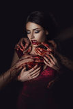 Girl vampire. In passionate embrace man's hands, stained with blood, the girl in a red dress, a fashionable toning, creative color stock image