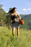 Sexy girl walk away with basket and flowers Royalty Free Stock Photos