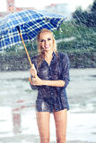 Sexy girl walking along wet street after rain Stock Photo
