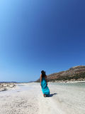 Sexy girl walking on the beach in a turquoise dress. Beautiful woman in turquoise long dress walking on the beach of Balos lagoon Crete Greece Royalty Free Stock Photography