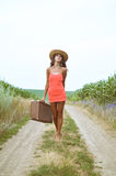 Sexy girl walking with old suitcase beside summer Stock Image