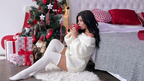 Girl drinking tea near Christmas tree in bedroom. stock footage