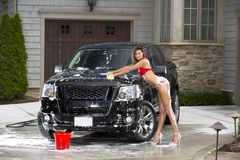 Sexy girl washes black truck in bikini Royalty Free Stock Photo