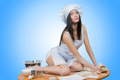girl wearing chef prepares dough. Royalty Free Stock Photos