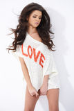 Sexy girl wearing LOVE sweater while posing on white Stock Photos