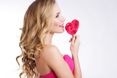 Sexy girl wearing pink dress with candy. Stock Photos