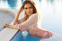 Sexy girl is wearing silk wet shirt in swimming Royalty Free Stock Photography