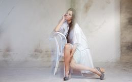 Sexy girl in white dress. Posing on chair Stock Photo