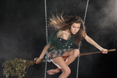 Sexy girl in witch costume sits on broomstick in smoke Royalty Free Stock Photography