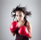 Girl woman athlet in red boxing gloves kicking. Beautiful young girl woman athlet in red boxing gloves kicking, studio portrait royalty free stock photo