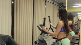 Sexy girl working on the cardio equipment in the gym. stock footage