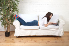Sexy girl works with notebook. Sexy girl lies on a soft divan and works with notebook Stock Photos