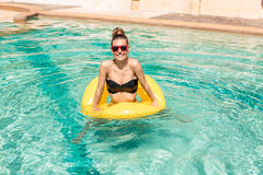 Sexy girl with yellow ring at pool party Royalty Free Stock Image