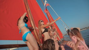 Sexy girls in bikini dancing on a yacht with red stock video