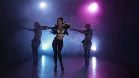 Sexy girls dancing in original outfit in lights. Smoky studio. Sexy girls dancing in original outfit in lights, dance group of three girls begin presentation stock footage