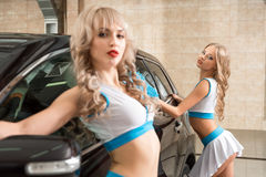 girls in formula one style posing at carwash stock photo
