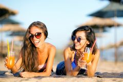 Sexy girls having fun on a beach. Two sexy girls drinking cocktails having fun on a beach Stock Photo