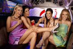 Sexy girls having party. In limousine, smiling, drinking Stock Photos