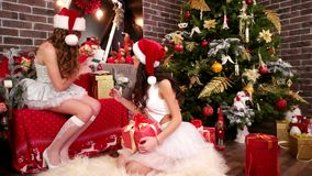 Sexy girls in Santa Claus hats near Christmas tree, Two friends wrapping festive boxes, On New Year`s Eve, sisters make stock video