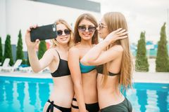 Sexy girls in swimsuits makes selfie near the pool Royalty Free Stock Images