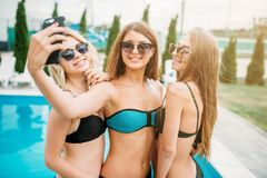 Sexy girls in swimsuits makes selfie near the pool Stock Photos
