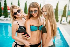 Sexy girls in swimsuits makes selfie near the pool Stock Image
